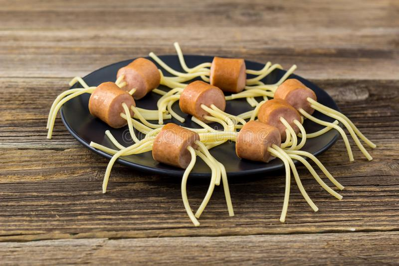 spaghetti with sausages in the form of spiders. Happy kid food for Halloween party stock photography