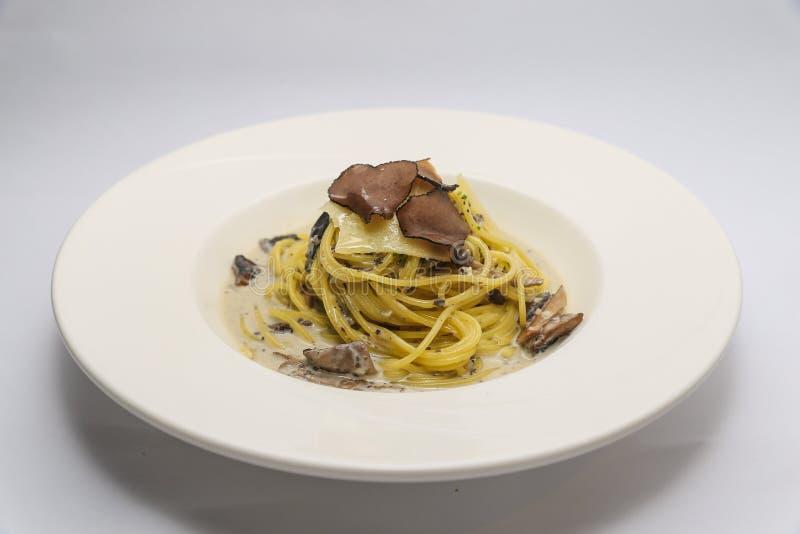 Spaghetti selvaggi del fungo del tartufo nero sul piatto bianco fotografia stock