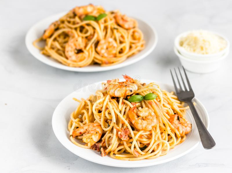 Spaghetti Shrimp Pasta on White Background Square Photo. Shrimp Spaghetti Pasta on a White Plate and White Background with Cheese in a Bowl royalty free stock photography