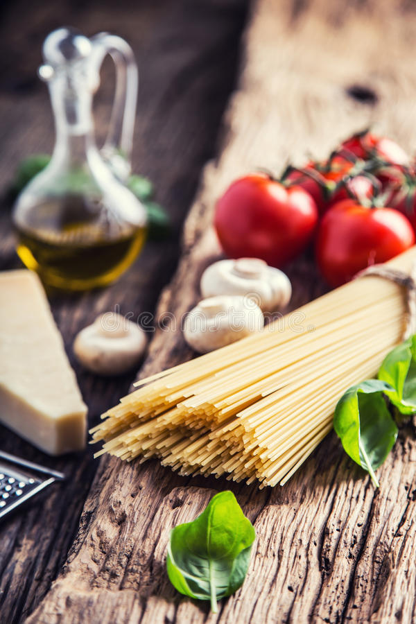 Spaghetti.Spaghetti tomatoes basil olive oil parmesan cheese and mushrooms on very old oak board. Mediterrannean cuisine and ingredients royalty free stock image