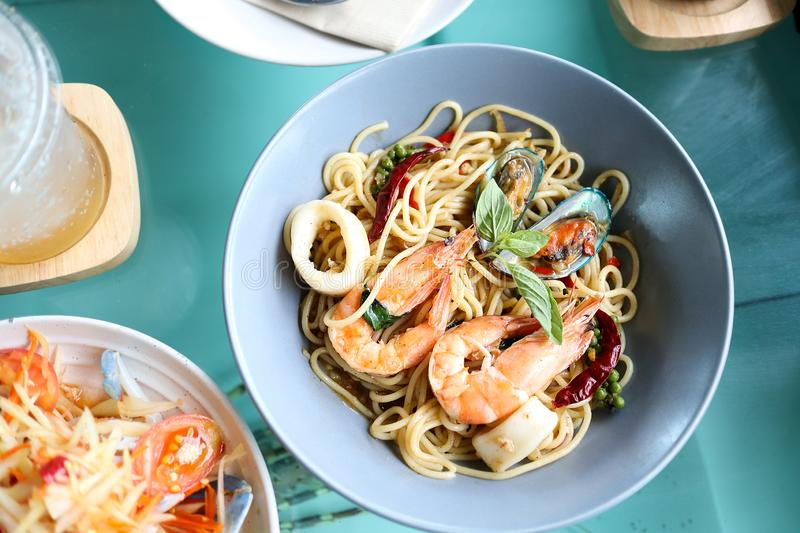 Spaghetti spicy seafood in blue dish on the table. Spaghetti spicy seafood in blue dish on the table top view stock photography