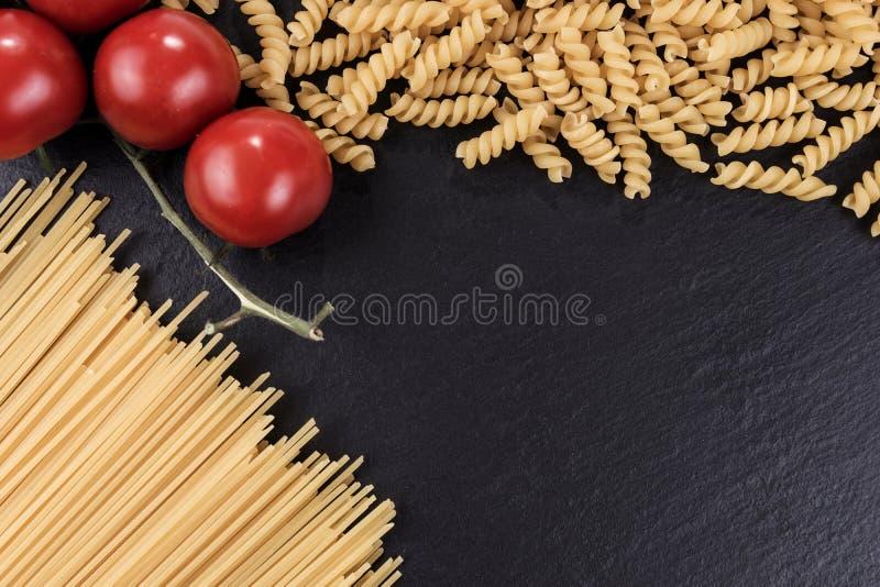 Spaghetti, spirelli and cherry tomatoes on black slate plate. Yellow raw spaghetti, spirelli and cherry tomatoes on black slate plate stock photo