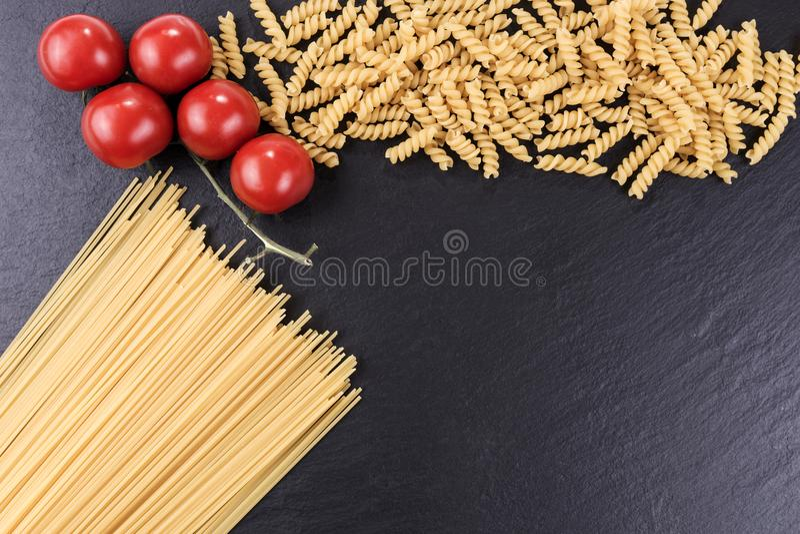 Spaghetti, spirelli and cherry tomatoes on black slate plate. Yellow raw spaghetti, spirelli and cherry tomatoes on black slate plate stock images