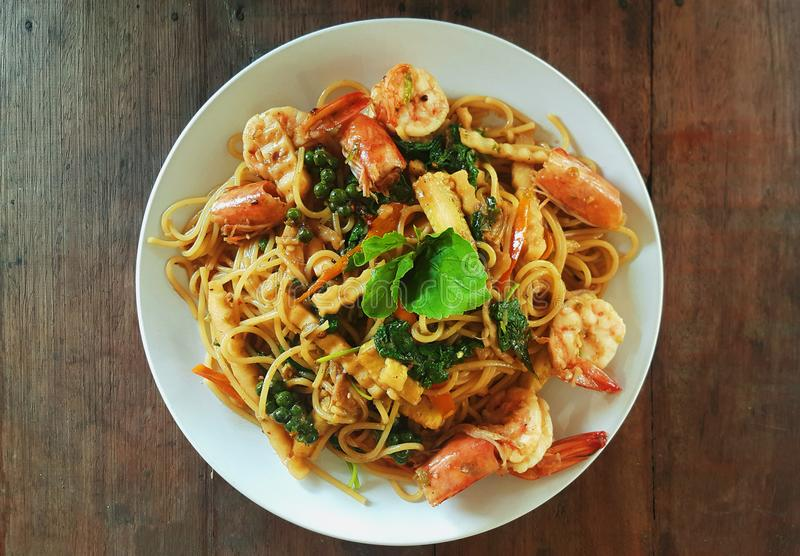 Spaghetti stir fried spicy thai pad ki mao with shrimp on wooden table. At home stock photo