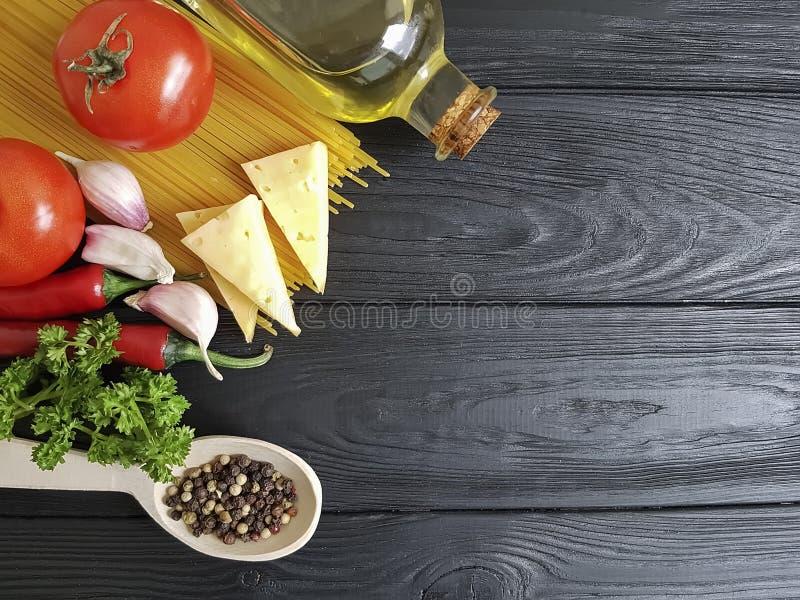 Spaghetti, tomate, ail, menu organique de pâtes de nourriture de recette de fromage un fond en bois noir photos libres de droits