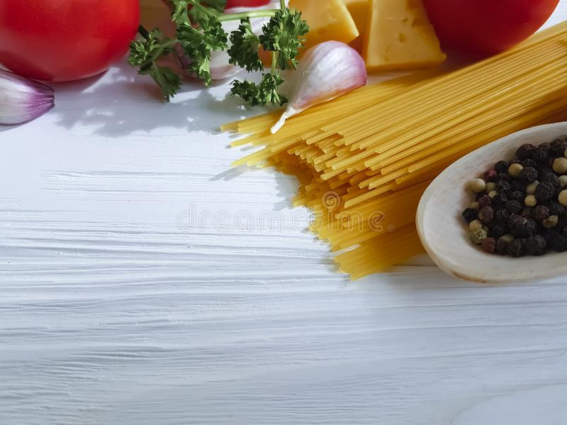 Spaghetti, tomato, garlic, pepper, butter, ingredient frame dinner cheese on a wooden background. Spaghetti tomato garlic pepper butter cheese on a wooden royalty free stock image
