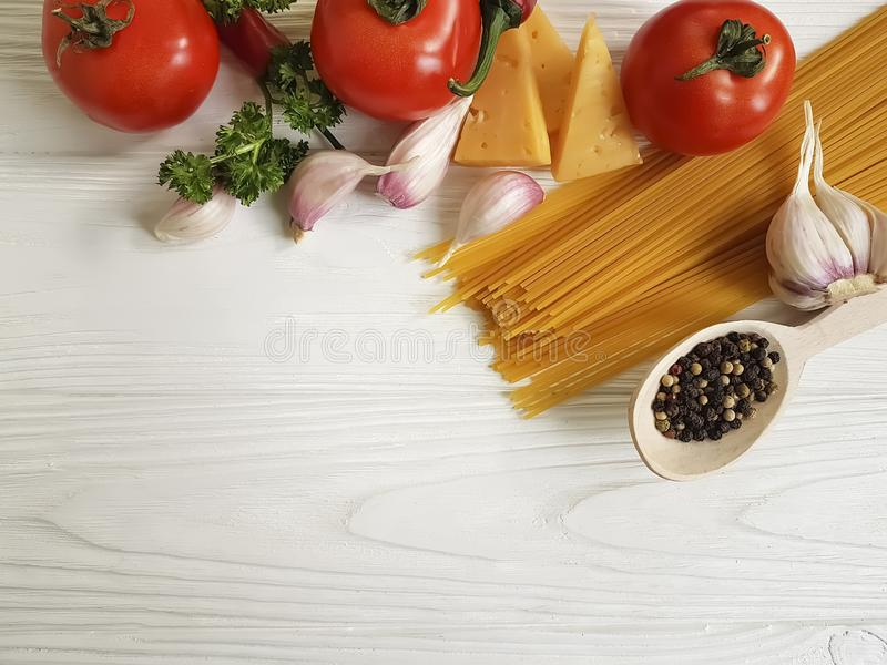 Spaghetti, tomato, garlic, pepper, butter, healthy dinner cheese on a wooden background. Spaghetti tomato garlic pepper butter cheese on a wooden background stock photo