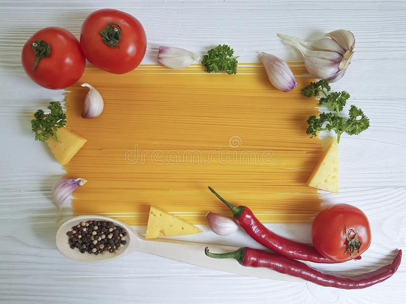 Spaghetti, tomato, garlic, pepper kitchen cheese menu on a white wooden background, cooking royalty free stock photography