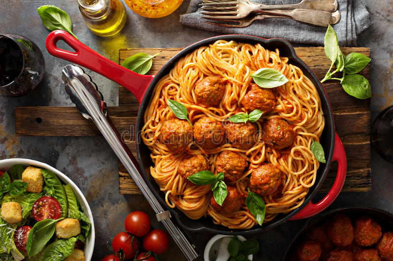 Spaghetti with tomato sauce and meatballs. Fresh vegetable salad and red wine overhead shot stock photo