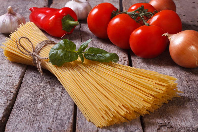 Spaghetti, tomatoes and basil on old table closeup stock photo