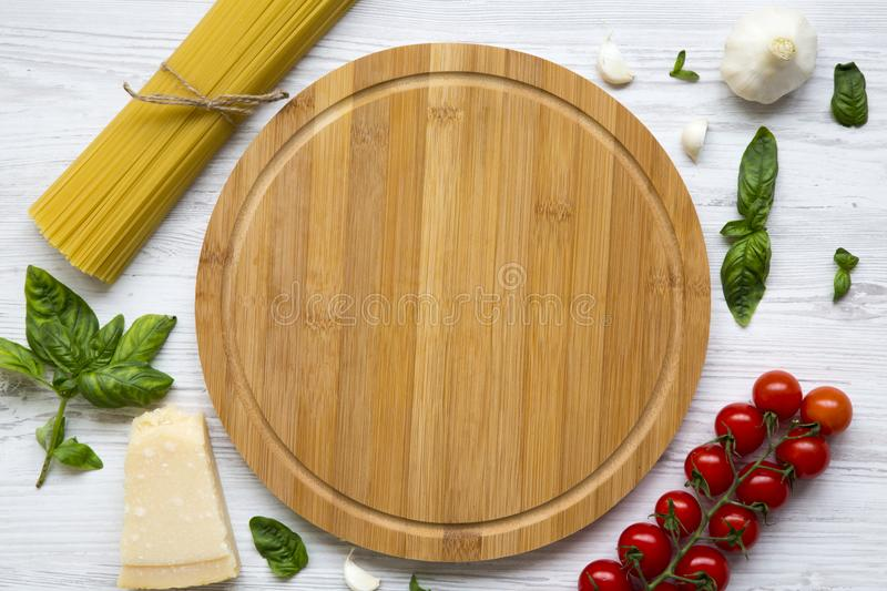 Spaghetti, tomatoes, basil, parmesan, garlic. Round board in the center. Ingredients for cooking pasta on a white wooden table, fl royalty free stock photo