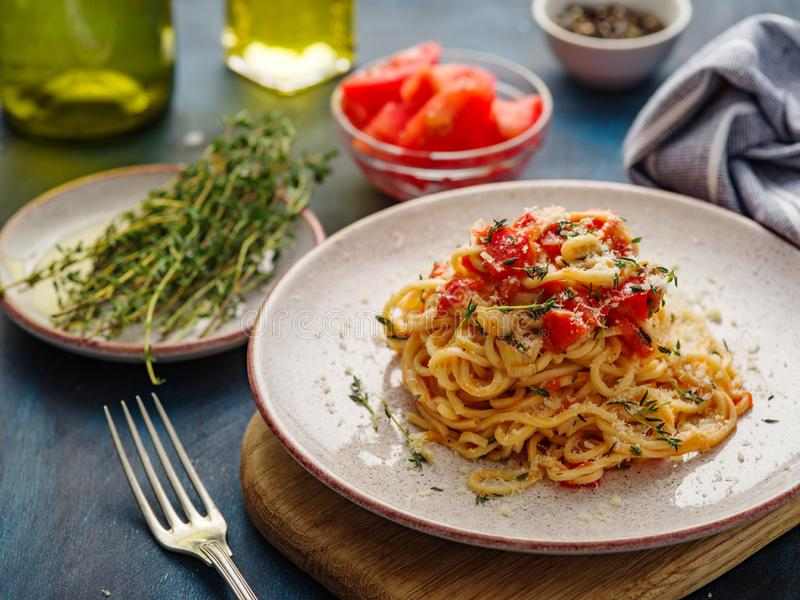 Spaghetti with tomatoes and thyme in a plate on a blue table royalty free stock images