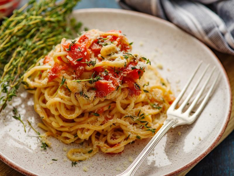 Spaghetti with tomatoes and thyme in a plate on a blue table stock photo