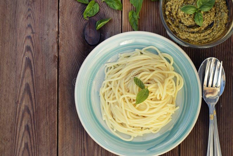 Spaghetti tradizionali italiani con la pasta di pesto del basilico con formaggio, pinoli, olio d'oliva, tavola rustica Copi lo sp fotografia stock