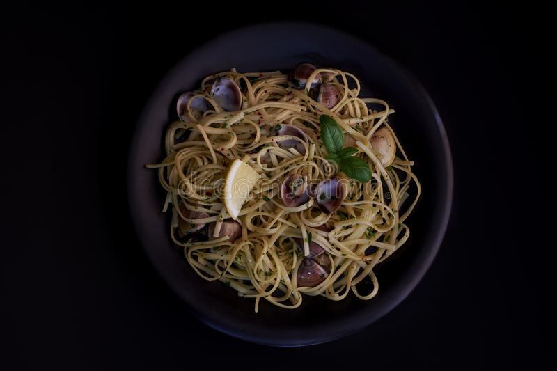 Spaghetti vongole, Italian seafood pasta with clams and mussels, in plate with herbs black background. Traditional Italian sea royalty free stock image