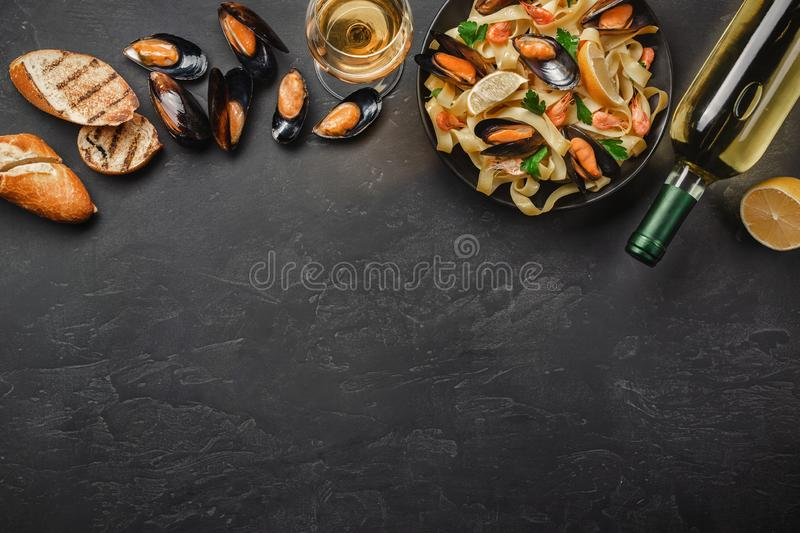 Spaghetti vongole, Italian seafood pasta with clams and mussels, in plate with herbs and bottle of white wine on rustic stone stock photos