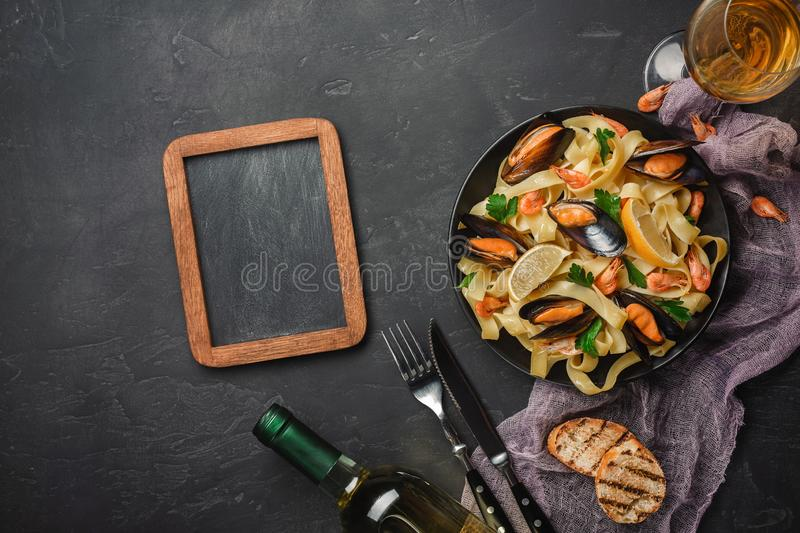 Spaghetti vongole, Italian seafood pasta with clams and mussels, in plate with herbs and glass of white wine on rustic stone royalty free stock photos