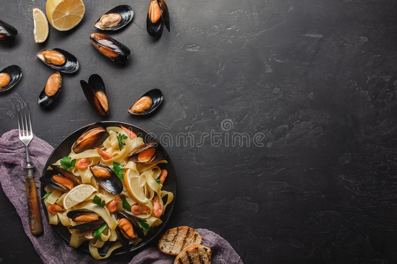 Spaghetti vongole, Italian seafood pasta with clams and mussels, in plate with herbs and glass of white wine on rustic stone royalty free stock photography