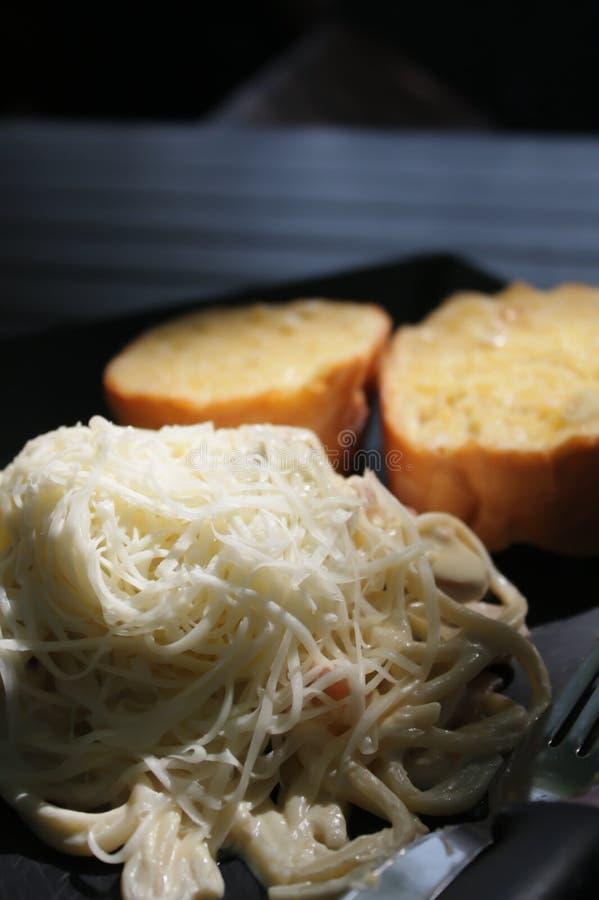 Spaghetti z białym kumberlandem, baleronem i pieczarkami nakrywającymi z, serem i czosnku chlebem słuzyć na czarnym talerzu obrazy stock
