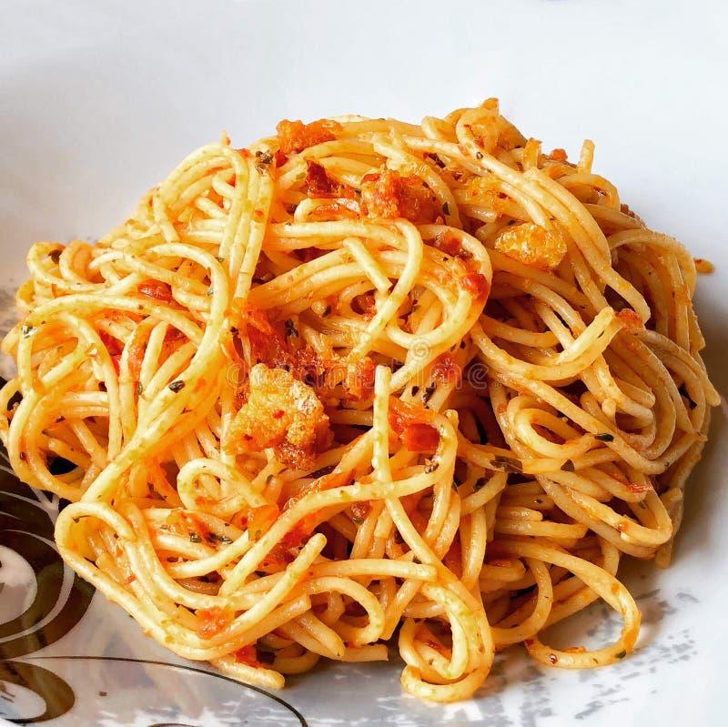 Spaghetti z czerwonym pesto kumberlandem i crispy wieprzowiną zdjęcia royalty free