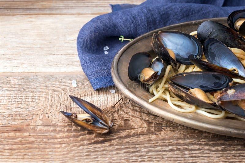 Spaghetti z mussels, pomidory w korzennym kumberlandzie w oryginału talerzu na starym drewnianym stole Milczka Mytilus zbliżenie zdjęcie stock