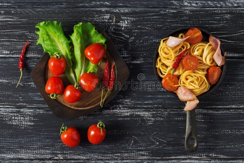 Spaghetti z pomidorem i baleronem słuzyć na małej żeliwnej smaży niecce, nieociosany tło Pomidory i liście sałata fotografia royalty free