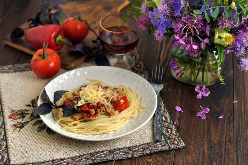 Spaghetti z serem, pomidorami, mięsem i basilem, Szkło czerwone wino obok go Warzywa i wildflowers Ciemny drewniany st?? obraz stock