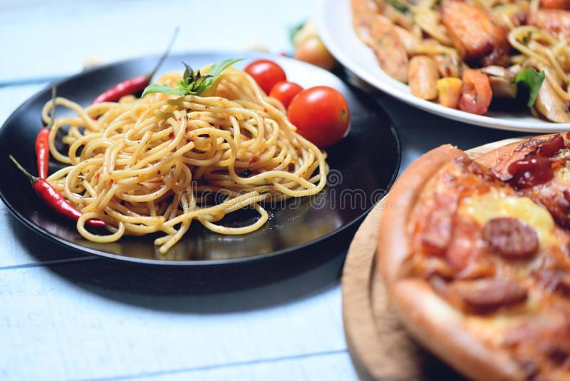 Spaghettideegwaren en pizza op houten dienblad - Traditionele heerlijke Italiaanse voedselspaghetti bolognese op plaat op de eett stock foto