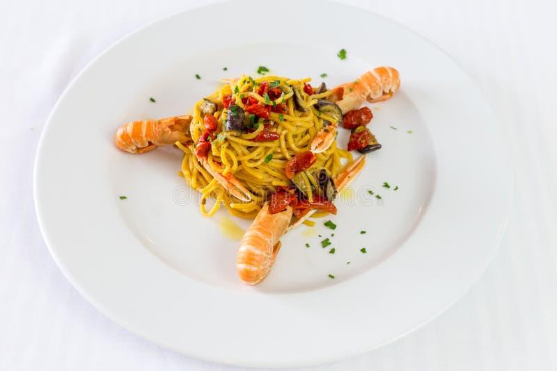 Spaghettideegwaren met garnalen en tomaten Gastronomische restaurantzeevruchten royalty-vrije stock fotografie