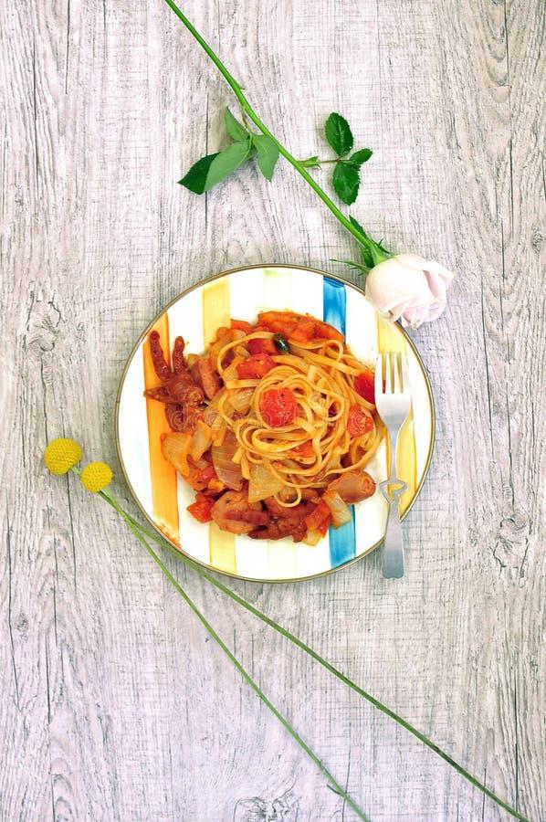 Spaghettideegwaren met tomatensaus op een houten achtergrond plaat hoogste mening stock foto's