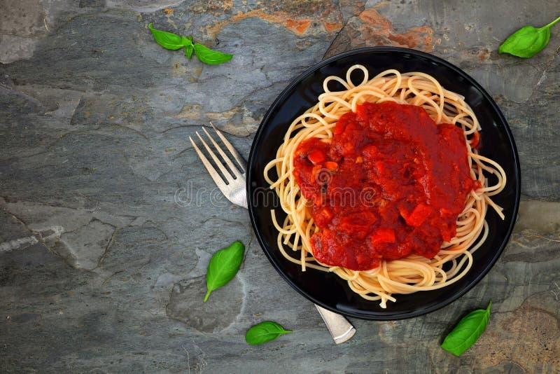 Spaghettideegwaren met tomatensaus, peper en paddestoelen, boven mening over donkere steen stock fotografie