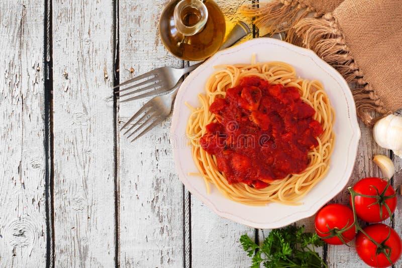 Spaghettideegwaren met tomatensaus, peper en paddestoelen, de hoogste grens van de meningshoek op een witte houten achtergrond me royalty-vrije stock afbeeldingen