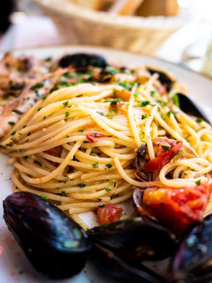 Spaghettis allo scoglio oder Spaghettis mit Meeresfrüchten dienten in einem weißen Teller mit Garnelen lizenzfreies stockbild