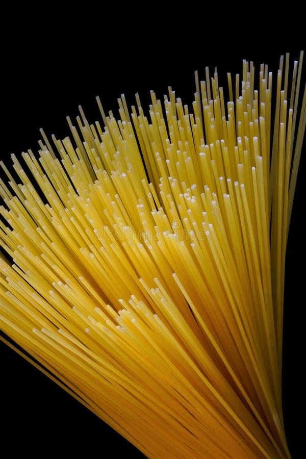 Spaghettis auf einem schwarzen Hintergrund, populäre Nahrung Spaghettis sind eine Art Teigwaren gemacht von getrocknetem Weizente lizenzfreie stockfotografie