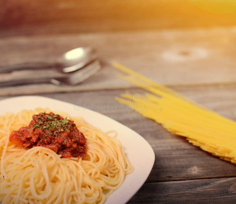 Spaghettis Bewohner von Bolognese mit Tomatenrindfleischsoße und rohen Teigwaren auf hölzernem Hintergrund stockbild