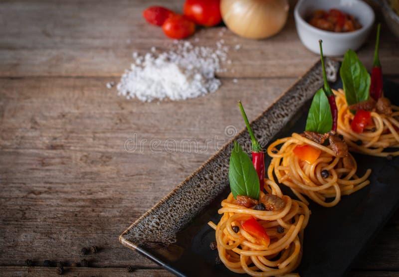 Spaghettis in der Tomatensauce passten die St?cke auf dem Schwarzblech, das auf die h?lzerne Tabelle dort gesetzt wurde, sind Tom stockfotos