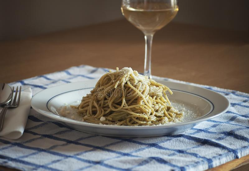 Spaghettis mit dem Pesto Genovese und Pecorino-Romanokäseglas Weißwein Vernaccia Toskana lizenzfreie stockbilder