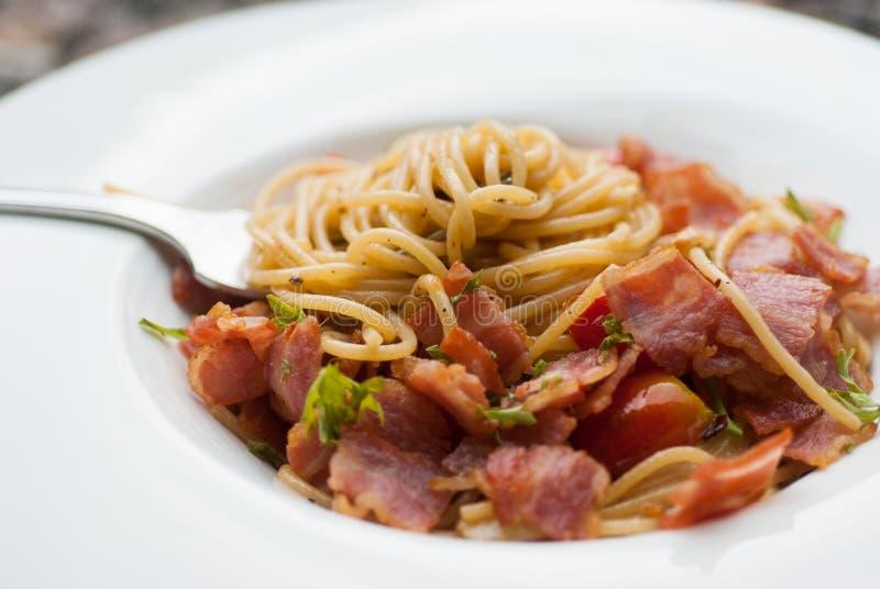 Spaghettis mit getrockneten Paprikas, Speck und Knoblauch stockbilder