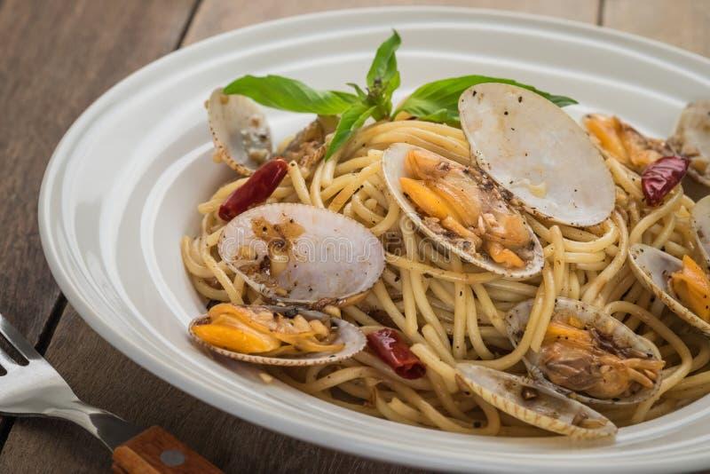 Spaghettis mit Muscheln in der Soße des schwarzen Pfeffers auf Platte lizenzfreie stockfotografie