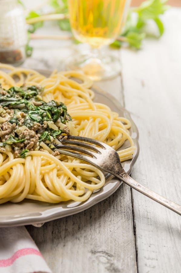 Spaghettis mit Spinat und Hackfleisch in der grauen Platte lizenzfreie stockfotos