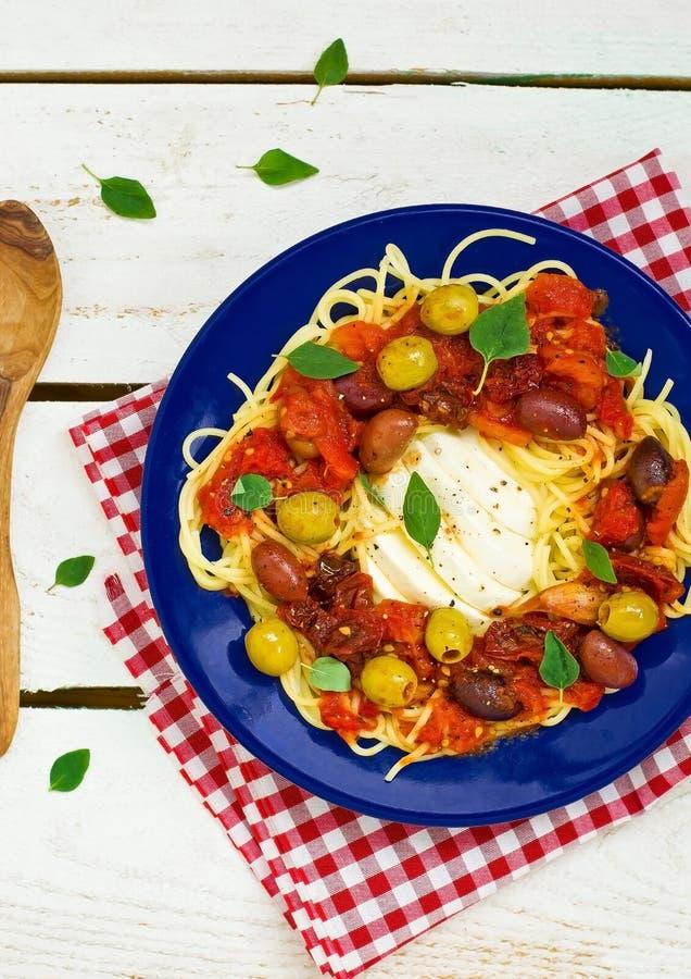 Spaghettis mit Tomatensauce und einem Mozzarella in einer Platte stockbild