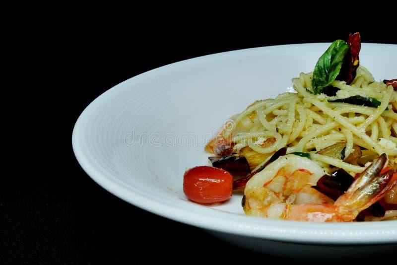 Spaghettis Olio mit Meeresfrüchteknoblauch trocknete Blätter des Paprikatomaten-Parmesankäseparmesankäses und des süßen Basilikum stockbild
