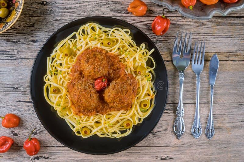 Spaghettis und Fleischklöschen mit Tomatensauce im schwarzen Teller auf hölzernem Hintergrund lizenzfreie stockfotos