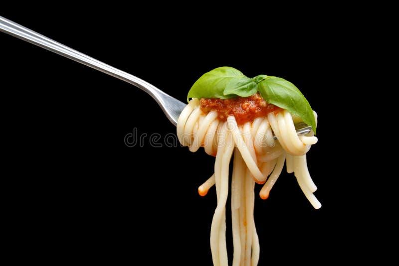 Spaghettis verwunden auf Gabel mit Basilikumblatt auf schwarzem Hintergrund lizenzfreies stockbild