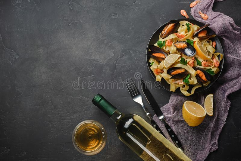 Spaghettis vongole, italienische Meeresfrüchteteigwaren mit Muscheln und Miesmuscheln, in der Platte mit Kräutern und Glas Weißwe lizenzfreie stockfotos