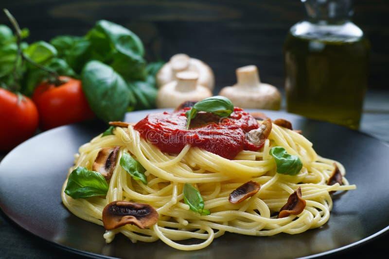 Spaghettiteigwaren mit Tomatensauce, gebratenen Champignons und Basilikum lizenzfreies stockfoto