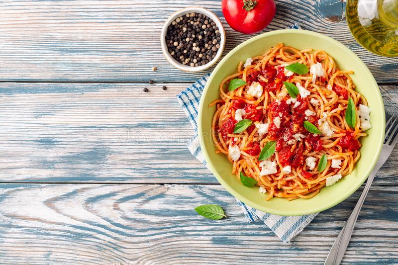 Spaghettiteigwaren mit Tomatensauce, Mozzarellakäse und frischen Basilikumblättern auf hölzernem Hintergrund der weiß-blauen Wein lizenzfreie stockbilder