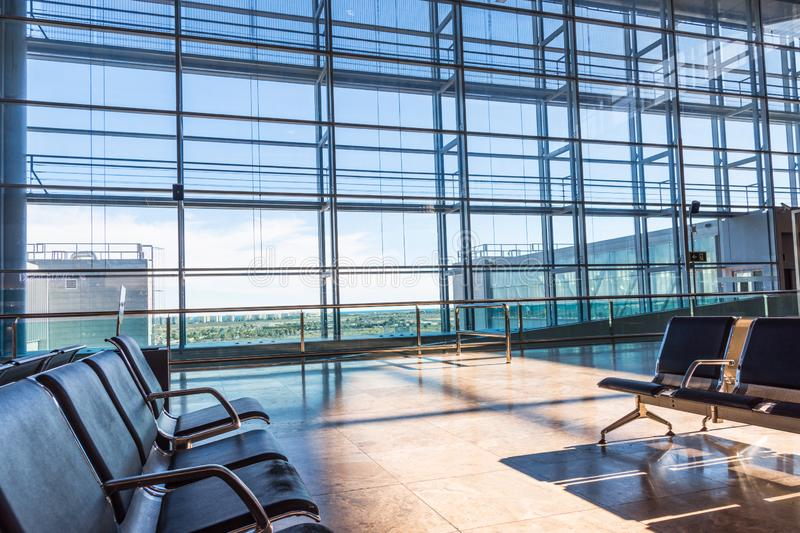 Airport lounge waiting area with no people. Rows of chairs big windows view onto landing field. Sunlight streaming through glass stock photos