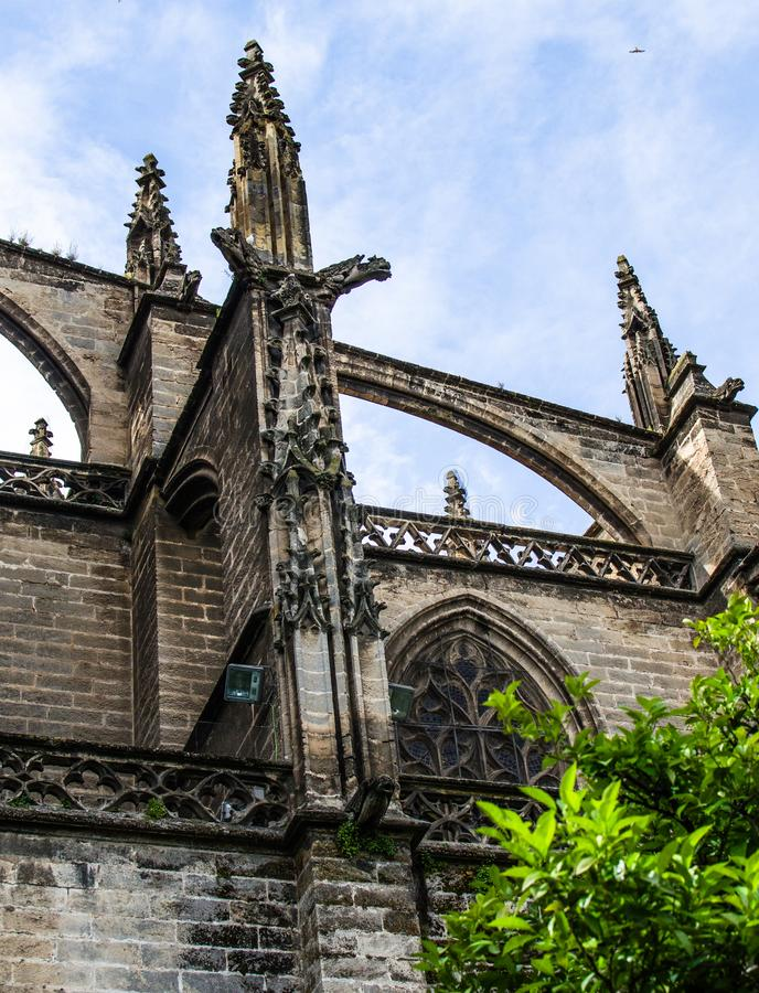 Spain, Andalusia, Seville Cathedral, outer walls with Gothic tracery windows, pointed spires royalty free stock images