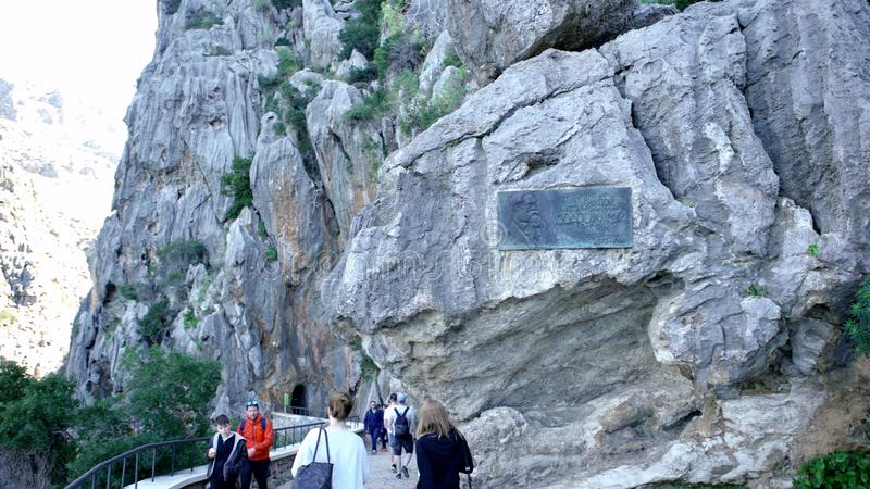 SPAIN, BARCELONA-13 APR 2019: Hiking trail with caves at foot of rocks. Art. Tourists enjoy beautiful mountain walk stock photo